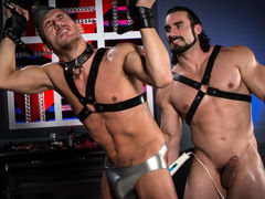 Athletic Alexander Gustavo's wrist restraints are tied to a spreader cane hanging above his head. Beefcake Jaxton Wheeler, covered in a full rubber uniform, spanks Alexander's ass, leaving his ass cheeks with a pink tinge. Grabbing an anal massager, Jaxto mature gay fuck